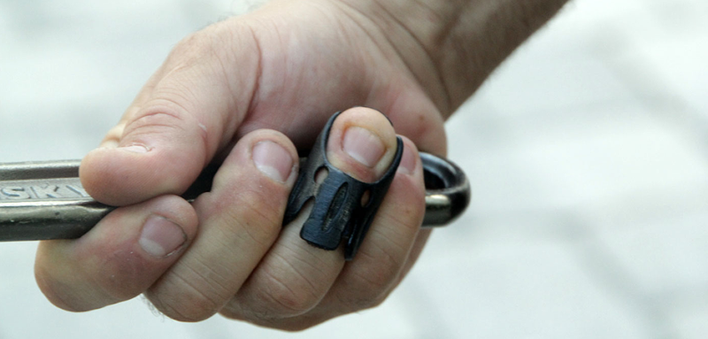 3D printed medical finger splint on a finger as the hand holds a tool