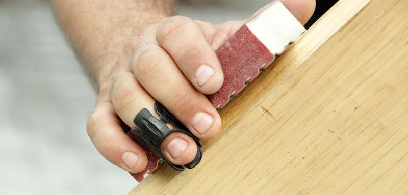 3D printed finger splint on a hand sanding wood